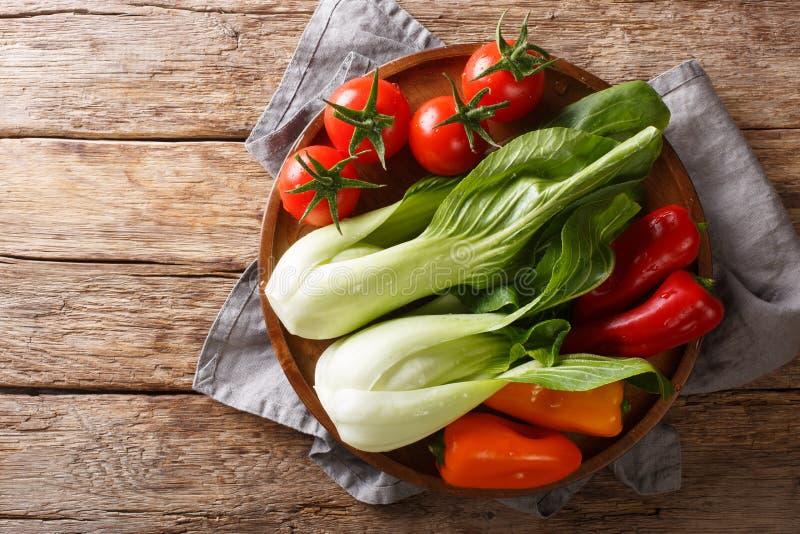 Bok frais de bébé d'ingrédients choy, tomates et poivrons en gros plan sur une table en bois vue supérieure horizontale images libres de droits
