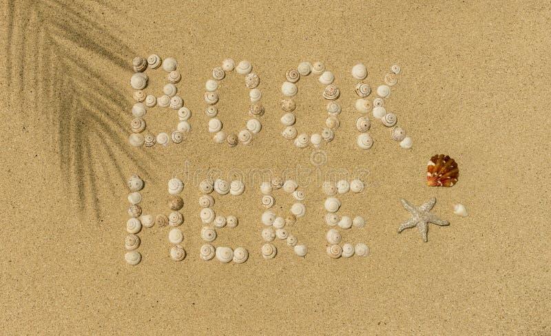 Bok här som är skriftlig i sand arkivfoton