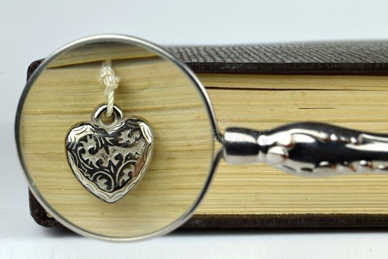 Bok, hjärta och förstoringsglas arkivfoton