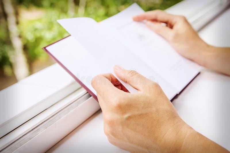Bok i händer av flickanärbilden arkivbild