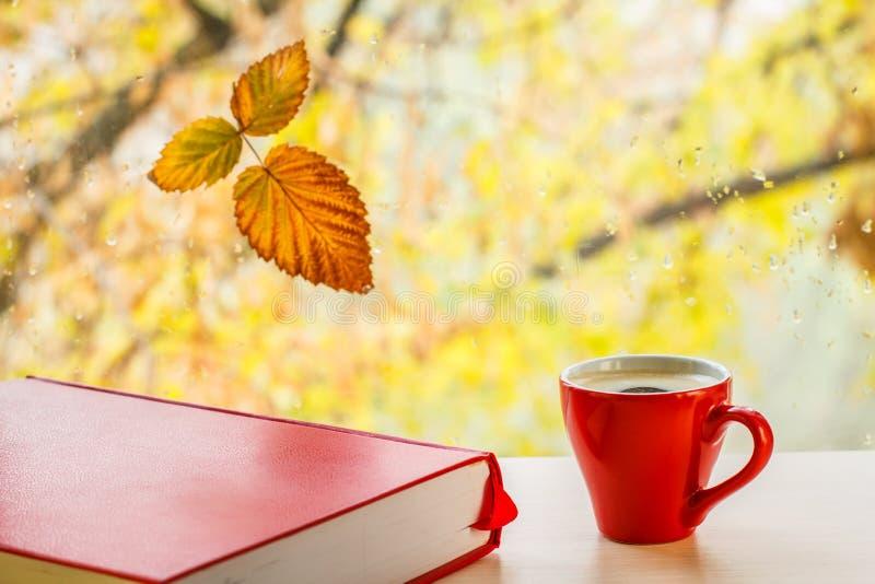 Bok, kopp kaffe och gult blad för höst på fönsterexponeringsglas med vattendroppar i den suddiga bakgrunden royaltyfri foto