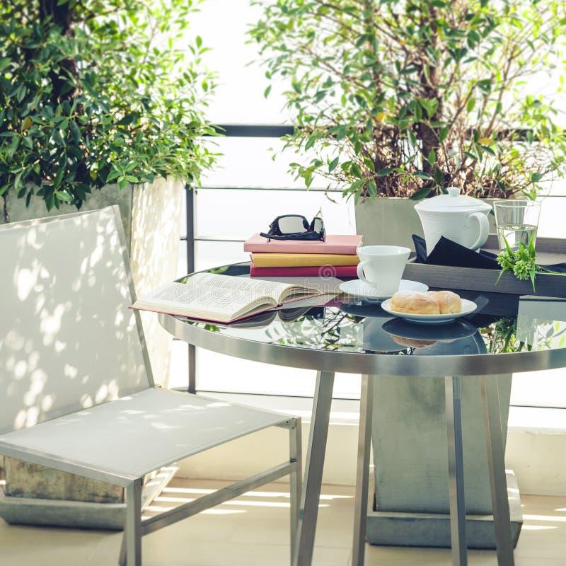 Bok på för terrasshem för tabell utomhus- garnering royaltyfri bild