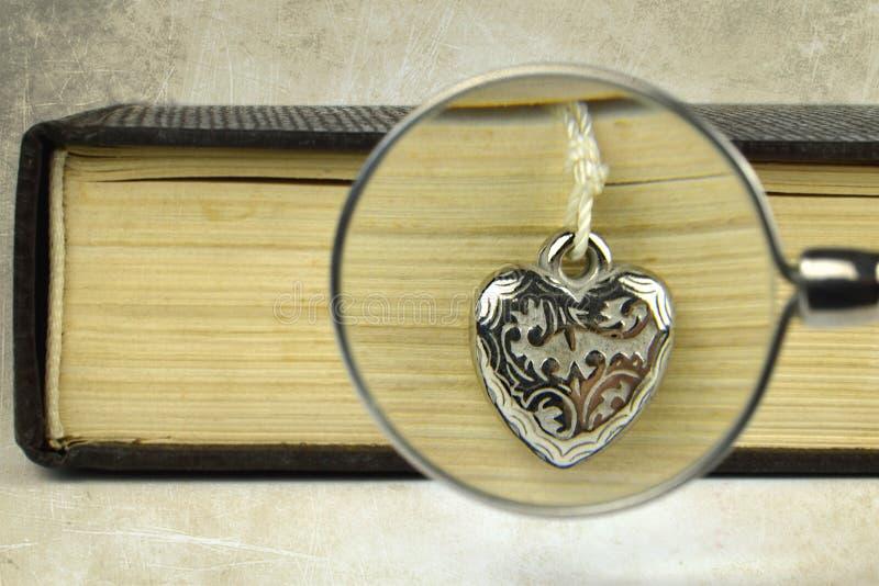 Bok, silverhjärta och förstoringsglas arkivbild