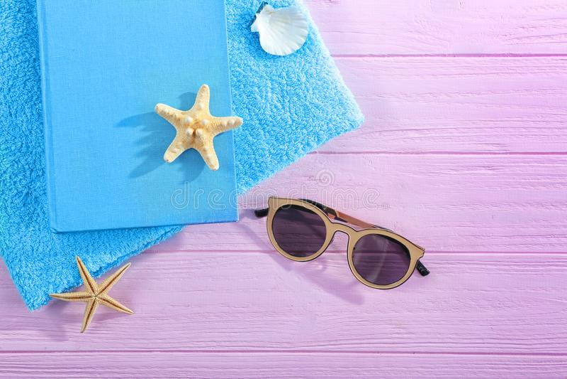 Bok, solglasögon och handduk arkivfoton