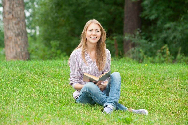 bok som läser utomhus kvinnabarn arkivfoton