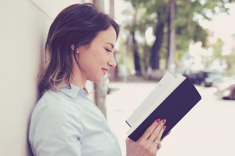 bok som läser utomhus kvinnabarn royaltyfri bild