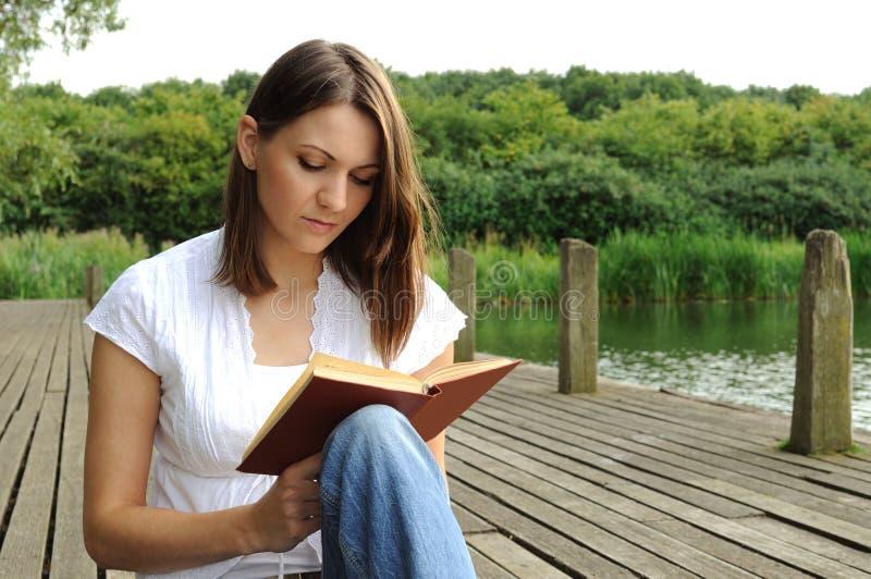 bok som läser utomhus kvinnan royaltyfria bilder