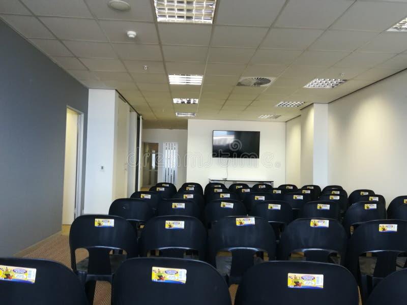 Boka ditt utrymme Stort konferensrum med tomma stolar arkivbilder