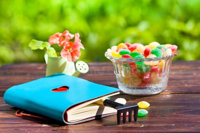 Boka med hjärta, monpase, krattar och blommar på tabellen i trädgård arkivbild