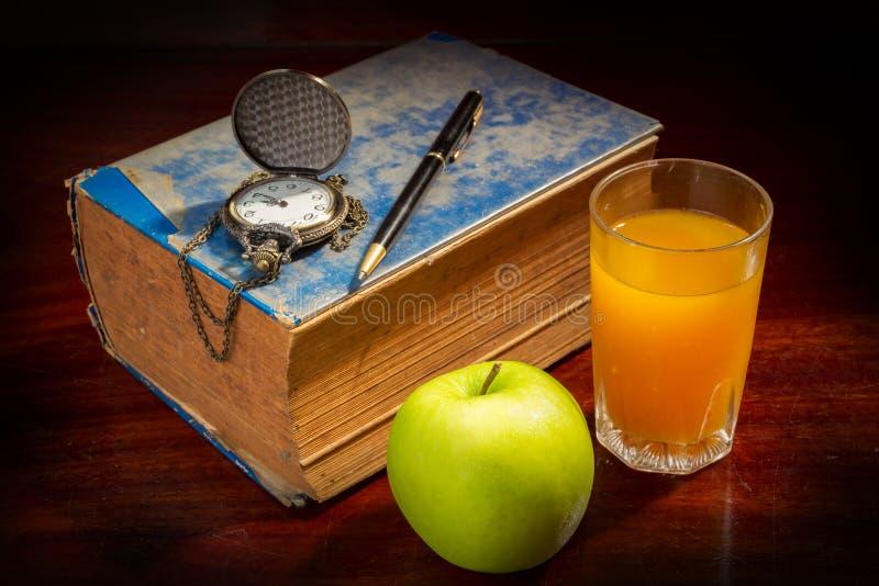 Boka med pennan, klockaäpplet och orange fruktsaft royaltyfri bild