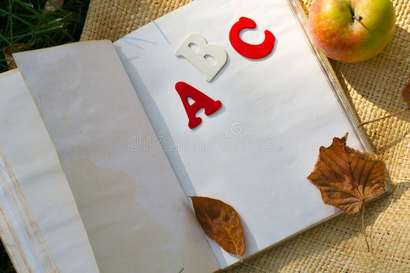 Boka och ett rött äpple på ett grönt gräs arkivfoton