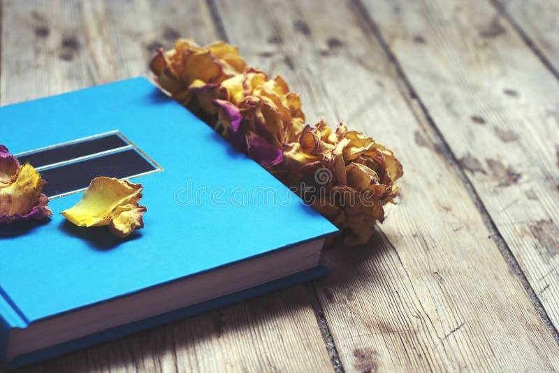 Boka på trägolvet med torra rosor fotografering för bildbyråer