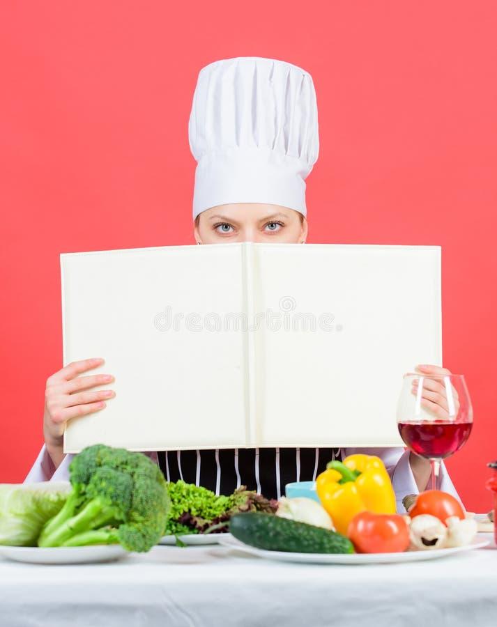 Boka varje hemmafru behöver i deras arkiv N?tt bok f?r kvinnal?sningkock i k?k Kökhembiträde som lär ny disk royaltyfri bild
