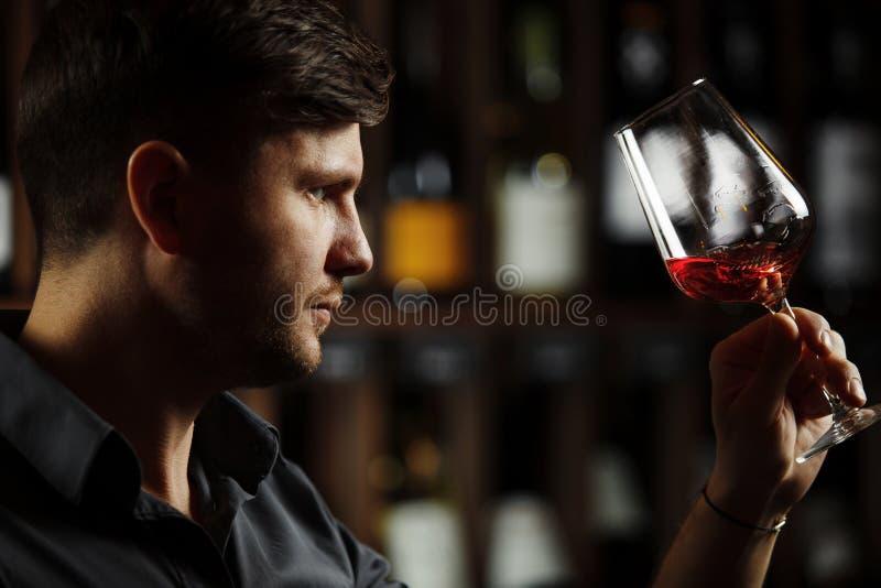 Bokal av r?tt vin p? bakgrund, manlig sommelier som uppskattar drinken arkivfoton