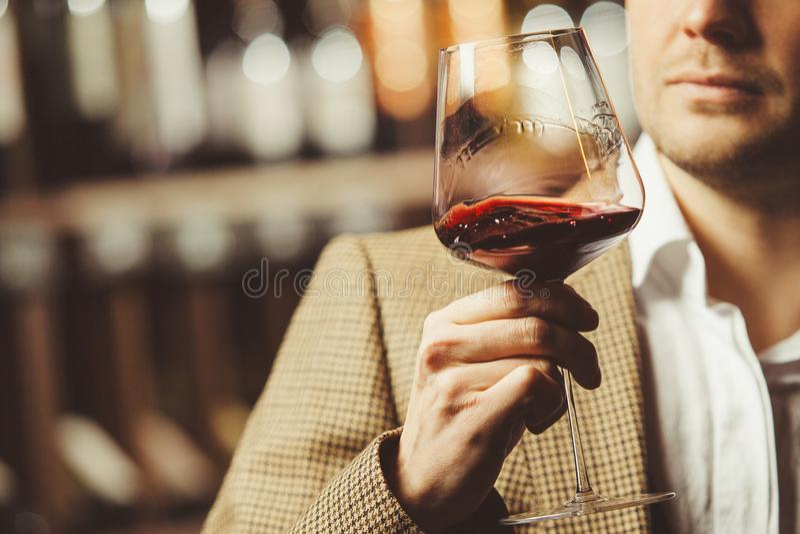 Bokal av r?tt vin p? bakgrund, manlig sommelier som uppskattar drinken royaltyfri fotografi