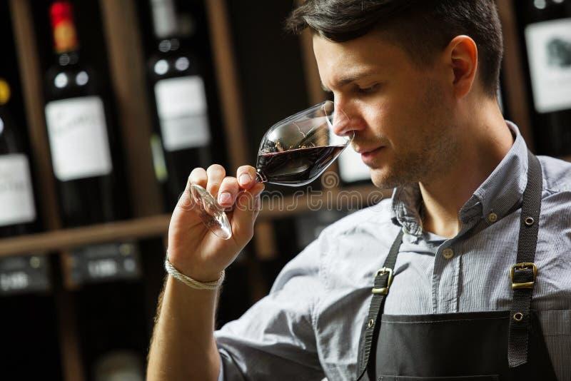 Bokal av r?tt vin p? bakgrund, manlig sommelier som uppskattar drinken arkivbild