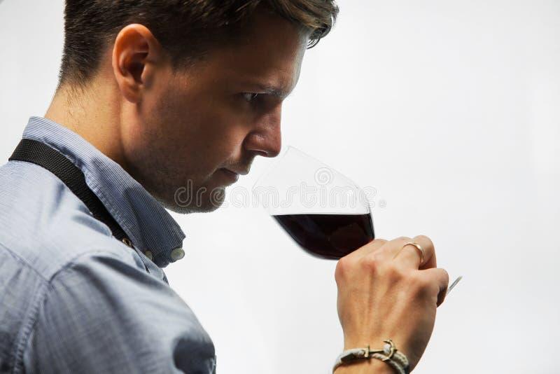 Bokal del vino rojo en el fondo blanco, sommelier masculino que aprecia la bebida foto de archivo