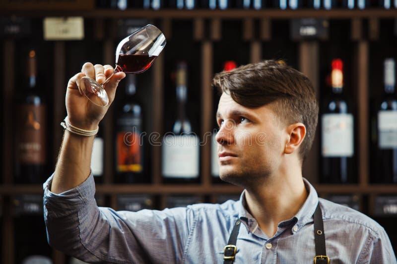 Bokal del vino rojo en el fondo, sommelier masculino que aprecia la bebida fotos de archivo libres de regalías