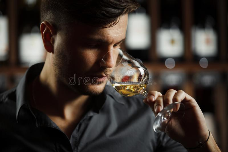 Bokal of white wine on background, male sommelier appreciating drink stock photo