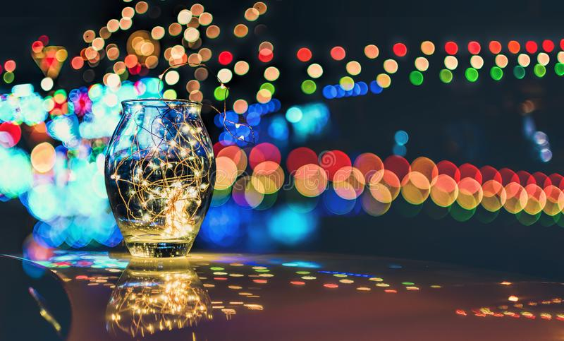 Bokeh abstrait des lumières de fête par un pot en verre au crépuscule photo stock