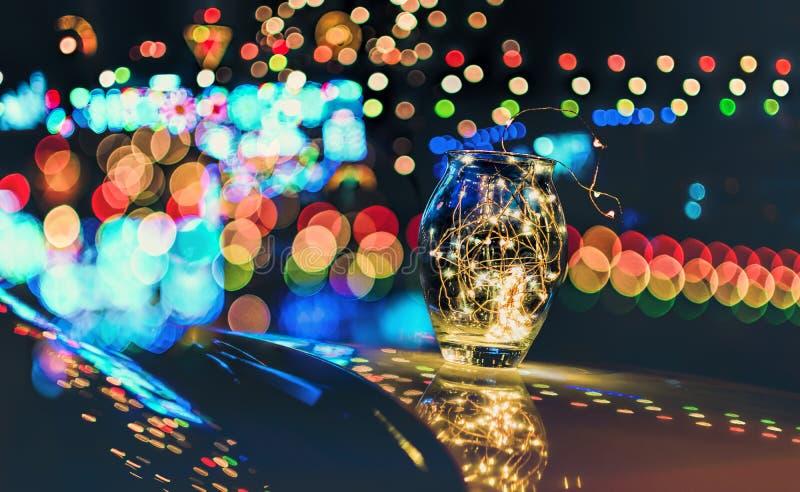 Bokeh abstrait des lumières de fête par un pot en verre au crépuscule photographie stock
