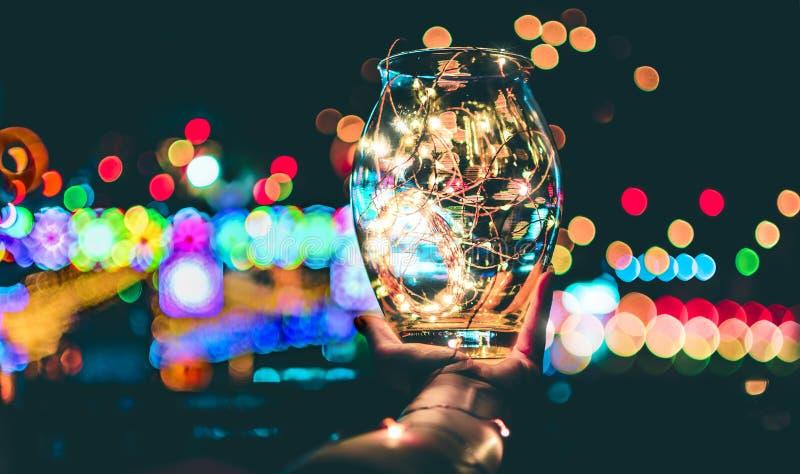Bokeh abstrait des lumières de fête par un pot en verre au crépuscule image libre de droits