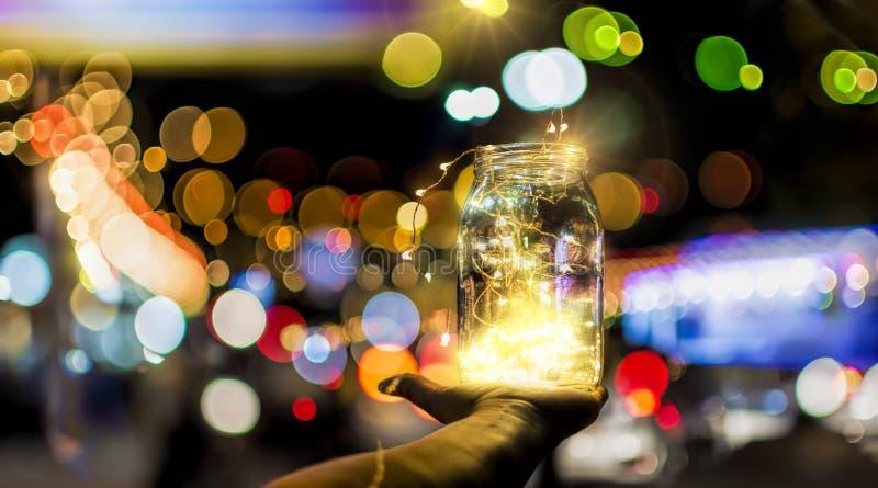 Bokeh abstrait des lumières de fête par un pot en verre au crépuscule images stock
