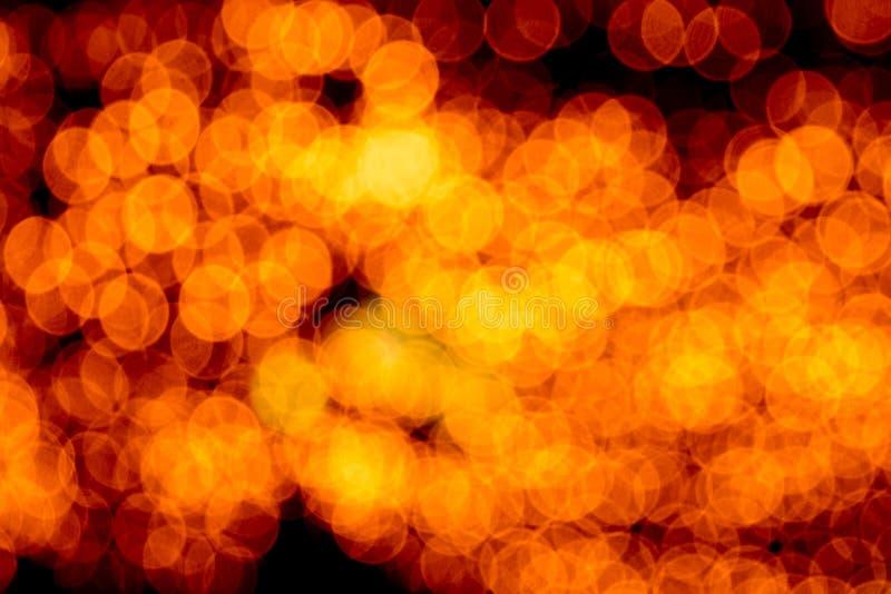 Bokeh arancio astratto Unfocused su fondo nero defocused e vago molti intorno a luce fotografie stock libere da diritti