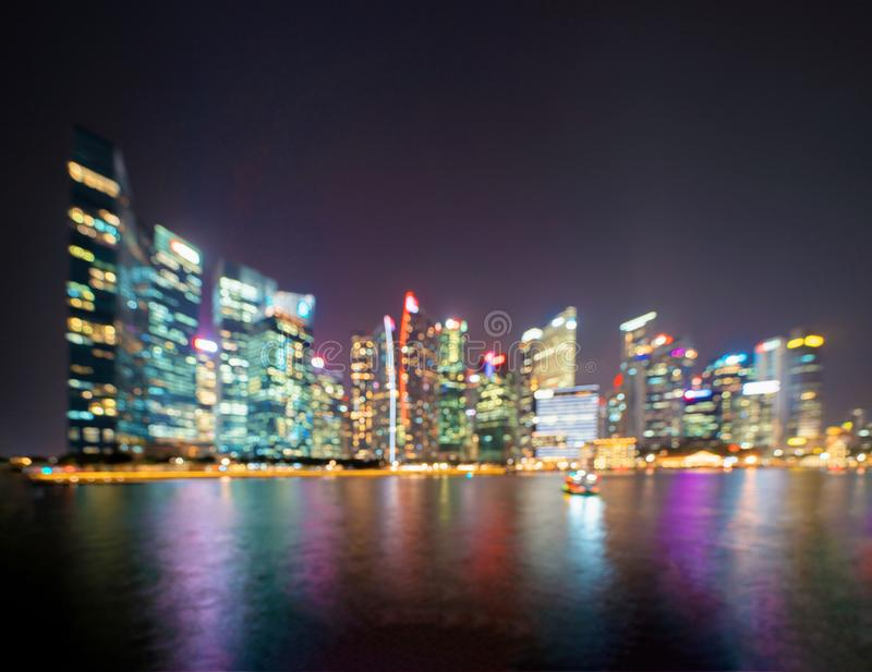 Bokeh background of skyscraper buildings in Singapore City Downtown with lights, Blurry photo at night time. Cityscape.  stock photos