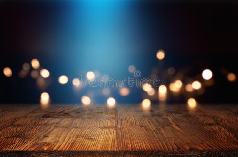 Bokeh bakgrund med den blåa ljusa strålen och en trätabell royaltyfri fotografi