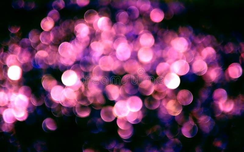 Bokeh blu rosa astratto su fondo nero Il bello bokeh circonda il modello su buio fotografia stock libera da diritti
