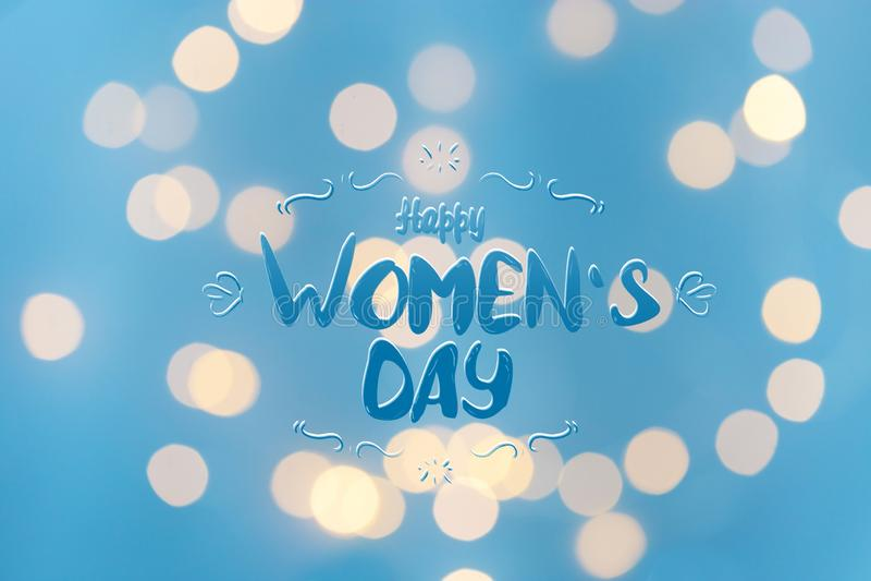 Bokeh brilhante com rotulação do dia das mulheres felizes em um espaço azul da cópia do fundo fotos de stock