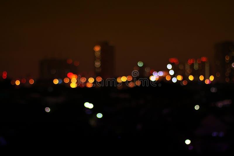 Bokeh coloré brouillé pour le fond de nuit, ville abstraite de tache floue de nuit avec le fond clair coloré de bokeh, rougeoyer  images libres de droits