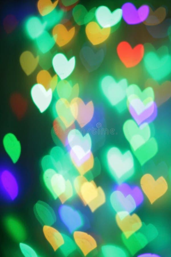 Bokeh colorido na forma dos corações imagens de stock royalty free