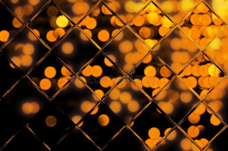Bokeh d'or sur le noir derrière le verre photographie stock libre de droits