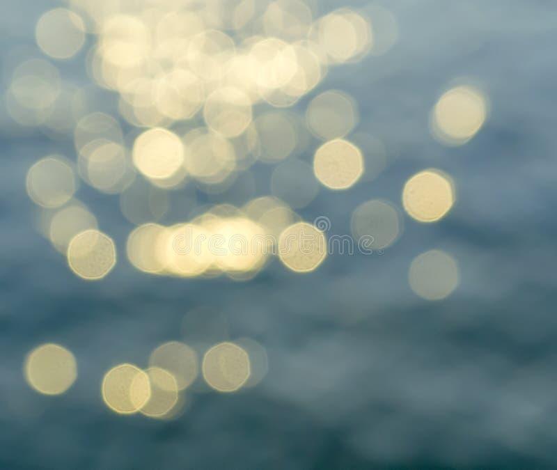 Bokeh da reflexão da luz do sol em uma superfície da água fotografia de stock