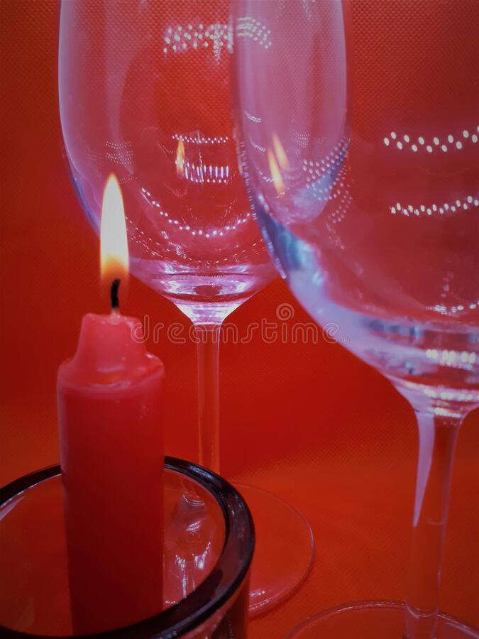 Bokeh effect, glass / crystal glasses and a candlestick with a red candle on a red abstract background royalty free stock image