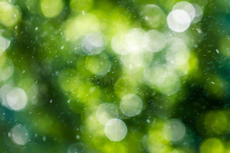 Bokeh en un fondo verde y pequeños descensos en el aire imagenes de archivo