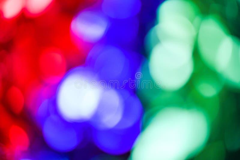 Bokeh ilumina o fundo colorido do bokeh com sumário verde do vermelho azul e do bokeh das luzes na árvore de Natal foto de stock