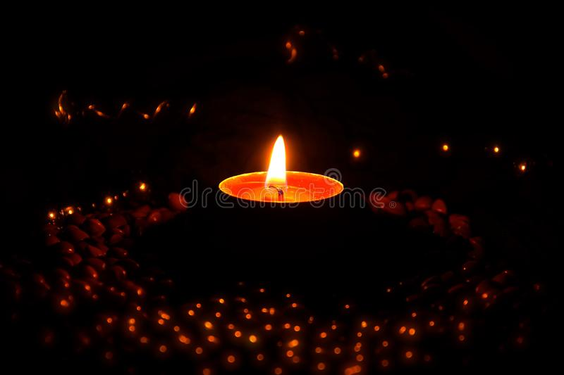 Bokeh image of burning tealight candle. Side view of a burning tealight candle  against a warm background of partially illuminated beads and metal objects stock photo