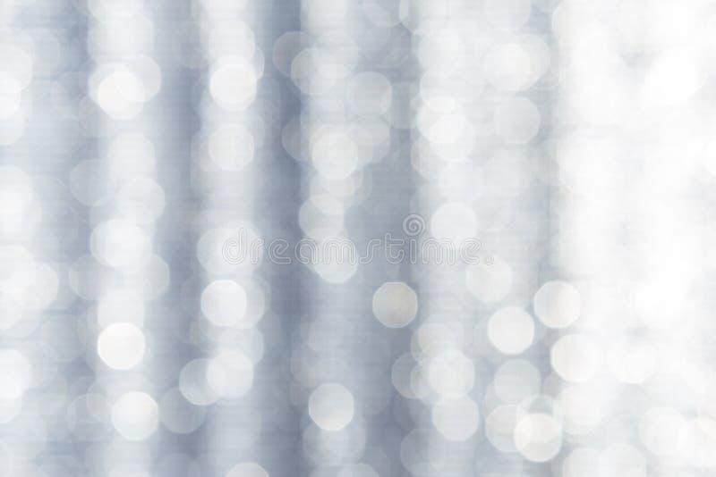 Bokeh leggero brillante astratto sopra fondo grigio vago immagini stock