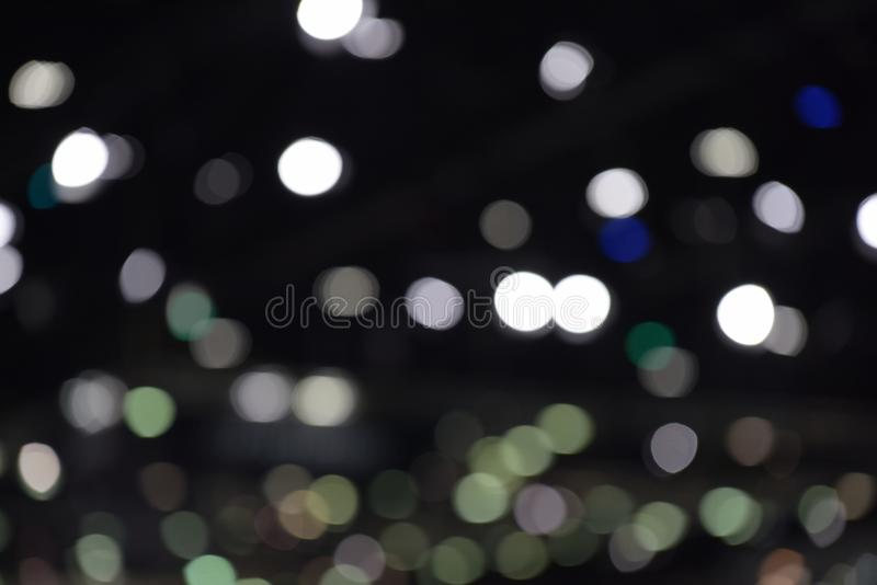 Bokeh of light in the car showroom at the motor show. Blurred images and beautiful bokeh of light in the car showroom at the motor show royalty free stock image