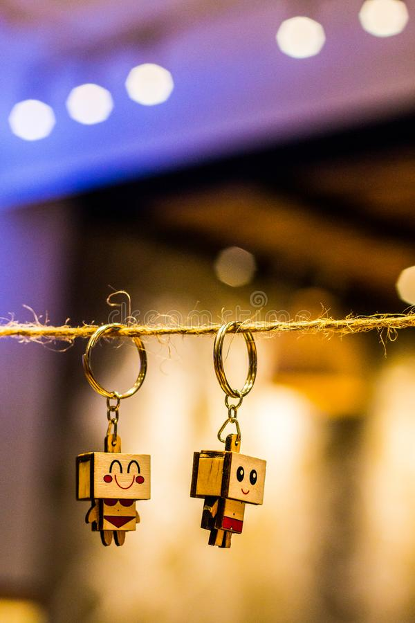 Bokeh Photography of Two Wood Block Man and Woman Figure Key Chains Hanging on Brown Thread royalty free stock image