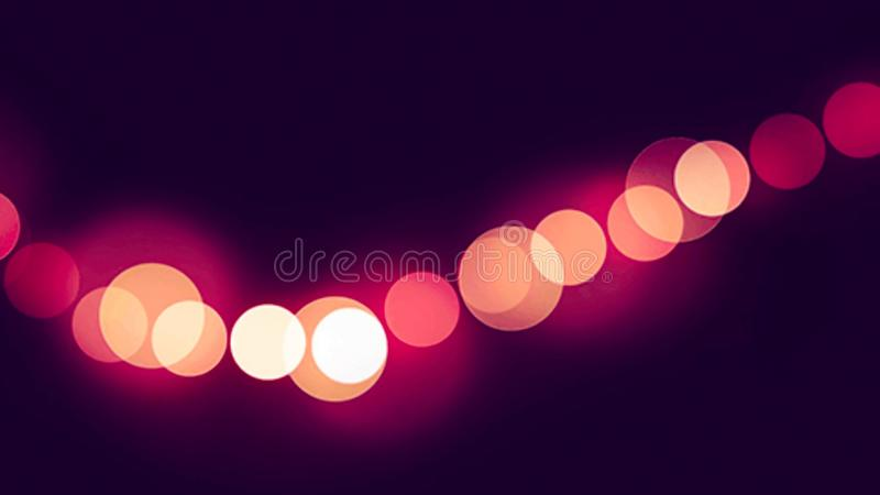 Bokeh rosa-chiaro su un fondo nero fotografia stock