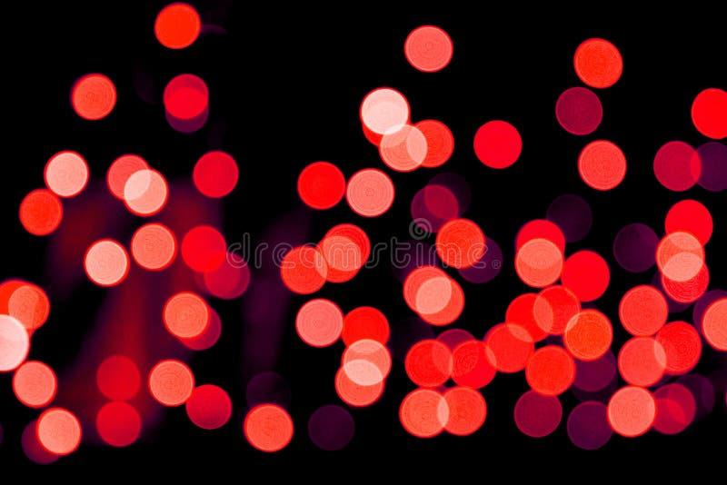 Bokeh rosso astratto Unfocused su fondo nero defocused e vago molti intorno a luce immagine stock