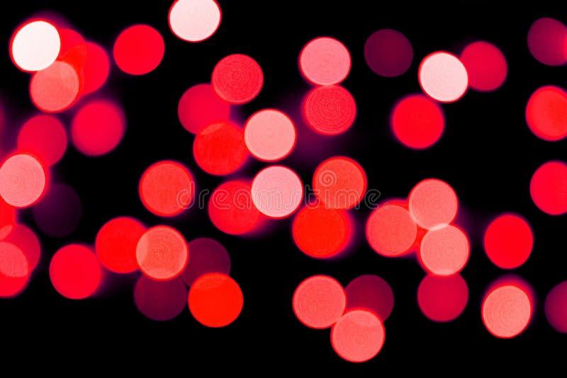 Bokeh rosso astratto Unfocused su fondo nero defocused e vago molti intorno a luce fotografie stock
