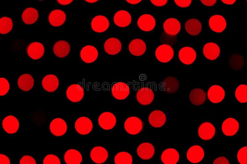 Bokeh rosso astratto Unfocused su fondo nero defocused e vago molti intorno a luce immagini stock