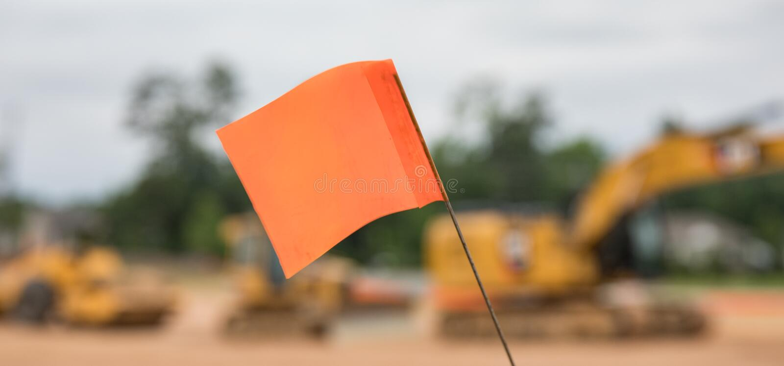 Bokeh shot of a warning flag in front of a row of heavy construction equipment. royalty free stock photo