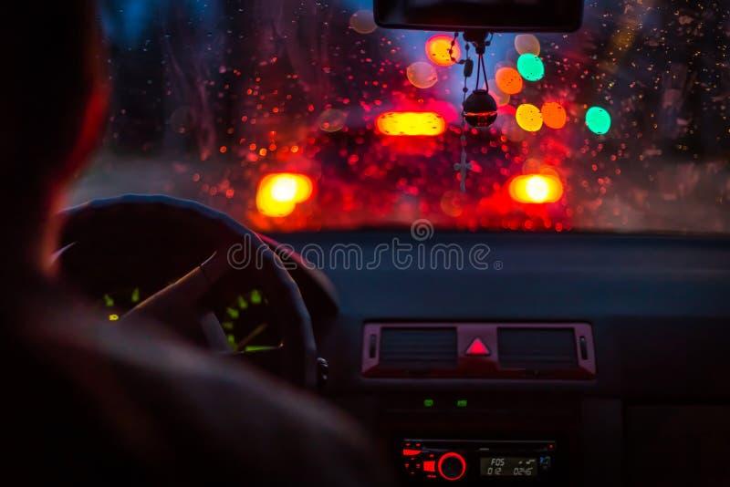 Bokeh tänder från trafikstockning till och med en bilvindruta på regnig natt i storstaden royaltyfri bild