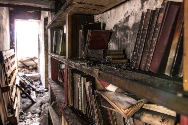 Boken brände i en bokhylla efter en brand fotografering för bildbyråer